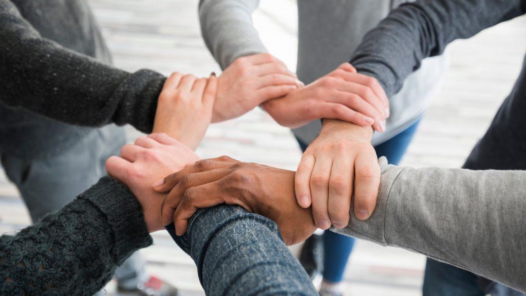 Grupo de personas entrelazando brazos