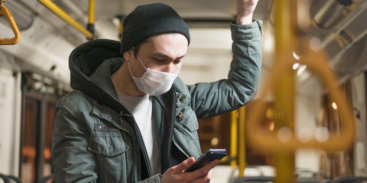 Chico en transporte público con mascarilla usando el móvil
