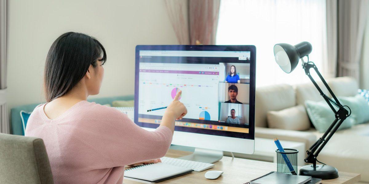 Chica trabajando en su ordenador mientras realiza una videoconferencia