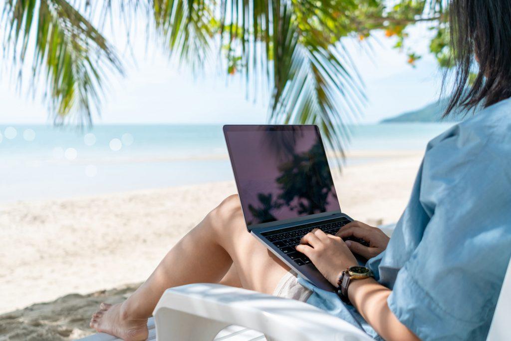 Mujer trabajando con un portátil en la playa