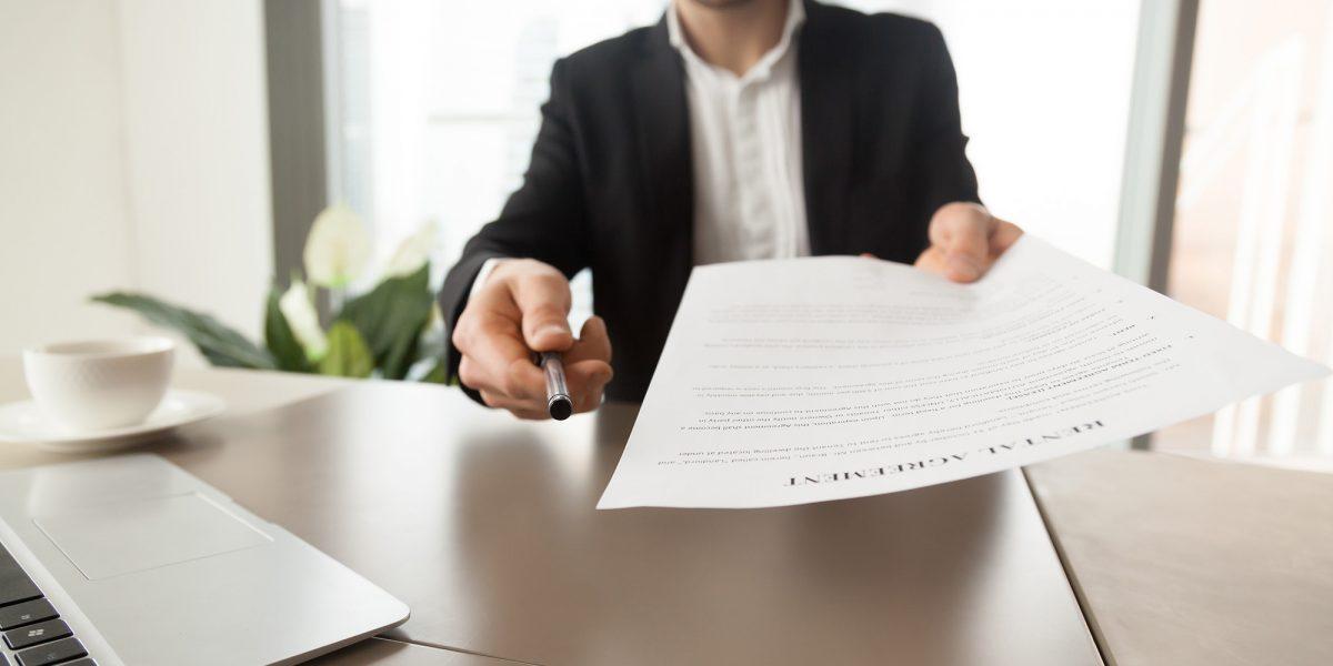 Un chico extiende un contrato y un bolígrafo para su firma