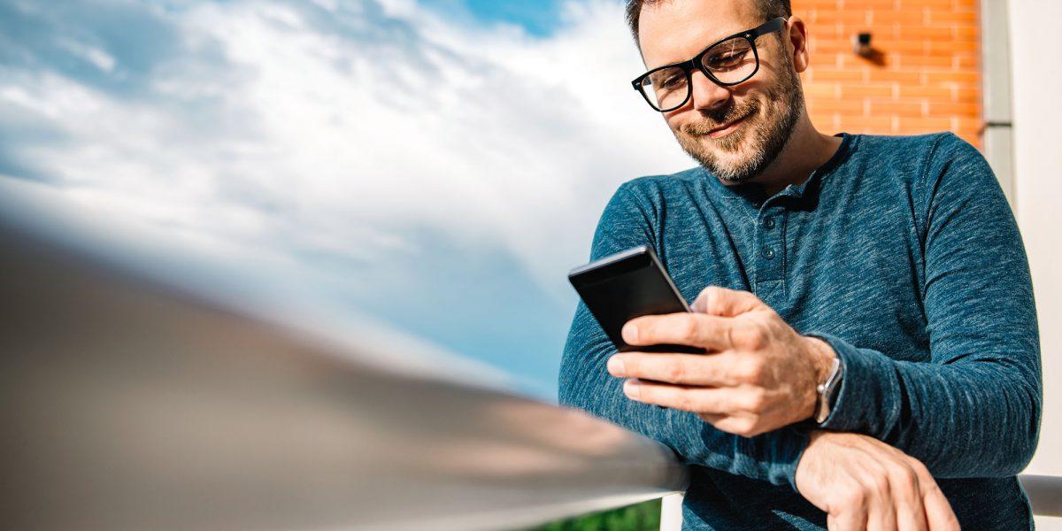 Hombre utilizando su teléfono móvil en un balcón