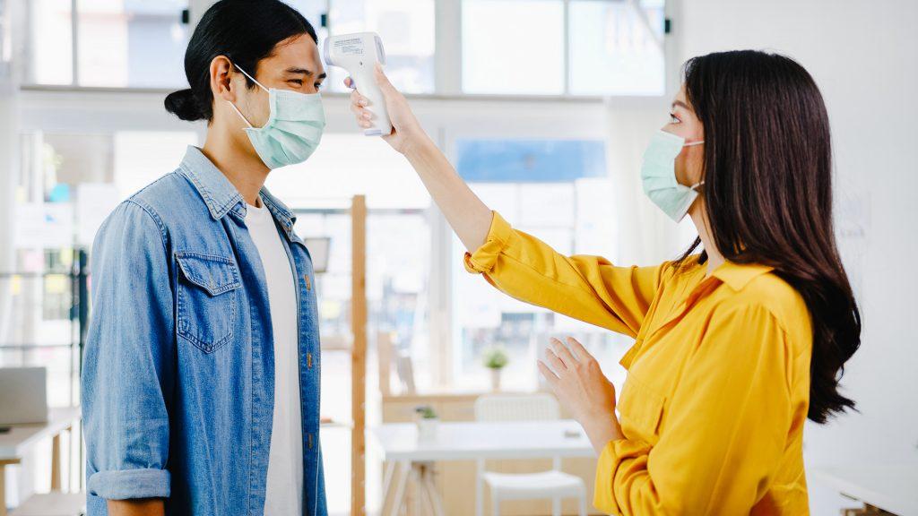 Una mujer le toma la temperatura a un chico, ambos llevan mascarilla