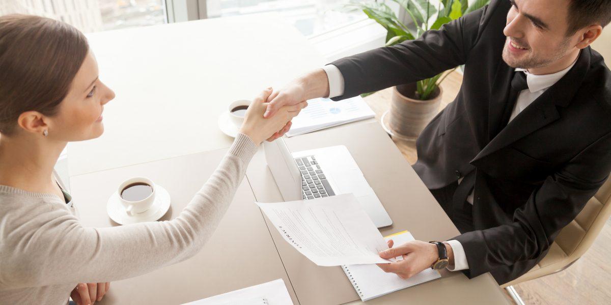 Dos personas estrechándose la mano en una entrevista de trabajo